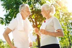 快乐的年迈的夫妇谈话在公园在体育活动以后 免版税库存图片