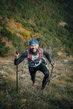 快乐的年轻运动员攀登与北欧人走的杆的一座山 库存图片