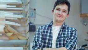 快乐的年轻workrer在微笑和看照相机的框架工作室车间 免版税库存照片