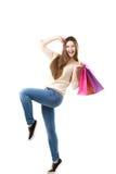 快乐跳舞与桃红色购物袋的美丽的十几岁的女孩 免版税库存图片