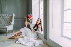 快乐,年轻新娘拿着与牡丹的土气婚礼花束在全景窗口背景 特写镜头纵向 A 免版税库存图片