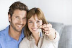 快乐30岁夫妇显示他们新的公寓钥匙  免版税图库摄影