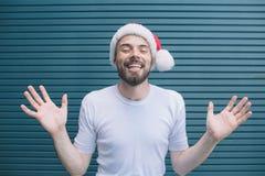 快活和好人显示他的手和手指在照相机 他保持眼睛闭上 人戴圣诞节帽子 他是 库存照片