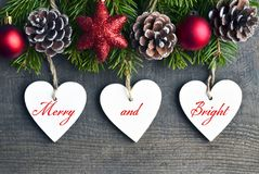 快活和明亮 与杉树、杉木锥体和白色木心脏的圣诞节装饰在老木背景 免版税库存照片