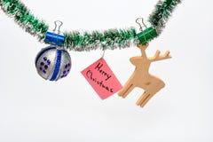 快活圣诞节的概念 与被别住的圣诞节装饰品和纸的闪亮金属片与笔记圣诞快乐,白色背景 免版税库存图片