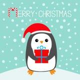 快活棒棒糖的圣诞节 在随风飘飞的雪的企鹅 圣诞老人红色帽子 配件箱礼品查出的白色 逗人喜爱的动画片kawaii滑稽的动物字符 平面 库存图片
