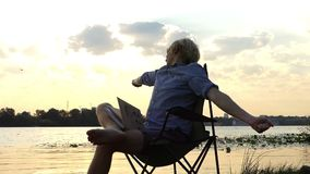 快活的人并且延长坐河岸在精采日落在Slo Mo 股票录像