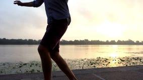 快活的人步行,舞蹈,在河岸转过来在日落在Slo Mo 影视素材