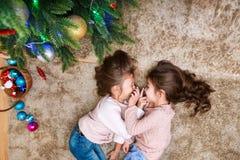 快活的圣诞节节日快乐 两逗人喜爱的女孩在家装饰圣诞树并且有乐趣室 免版税库存图片