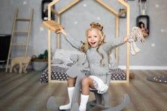快活的圣诞节节日快乐 打开圣诞节礼物的快乐的逗人喜爱的儿童女孩 免版税图库摄影