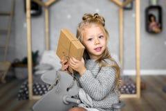 快活的圣诞节节日快乐 打开圣诞节礼物的快乐的逗人喜爱的儿童女孩 免版税库存照片