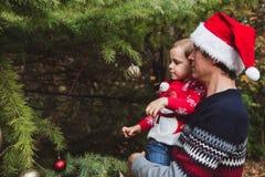 快活的圣诞节节日快乐 红色红色毛线衣的装饰圣诞树的圣诞节帽子和女儿的父亲室外 库存图片