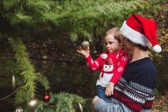 快活的圣诞节节日快乐 红色红色毛线衣的装饰圣诞树的圣诞节帽子和女儿的父亲室外 库存照片