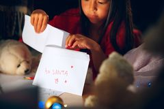 快活的圣诞节节日快乐 逗人喜爱的小孩女孩给圣诞老人项目写信在圣诞树附近 免版税图库摄影