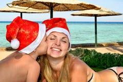 快活的圣诞节 妈妈和小儿子在戴圣诞老人帽子和庆祝圣诞节的海滩说谎 图库摄影