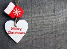 快活的圣诞节 装饰白色木圣诞节心脏和红色手套在灰色土气木背景 寒假概念 免版税库存照片