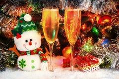 快活的雪人和葡萄酒杯用汽酒在圣诞树的背景 球,诗歌选,闪亮金属片 免版税库存照片