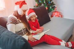 快活的Christamas和新年快乐 有红色帽子的少妇坐有女儿的沙发 她拿着在她的膝部的书 图库摄影