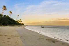 快艇被栓对海滩在日出 免版税库存照片