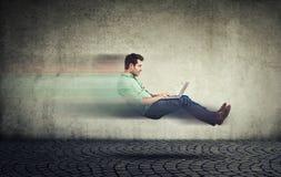 快速互联网 驾驶汽车技术的自治自已 路的浮动的商人使用膝上型计算机 免版税库存照片