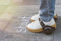 快速启动,在轮子穿上鞋子的脚 在Th的词起动白垩 免版税库存图片