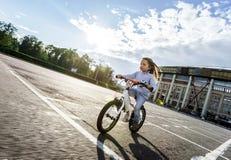 快速地乘坐乘自行车的逗人喜爱的小女孩 免版税库存图片