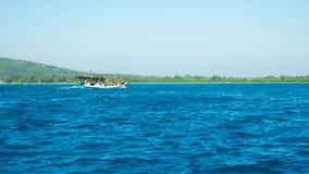 快速地移动与绿色海岛的一条传统小船作为在距离的背景 免版税库存图片
