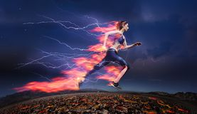快速地跑反对与闪光的风雨如磐的天空的妇女 免版税库存照片