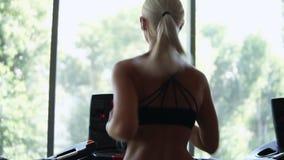 快速地跑在健身俱乐部的轨道踏车的罕见的观点的健身女孩 运动服的然后解决白肤金发的女孩 股票视频