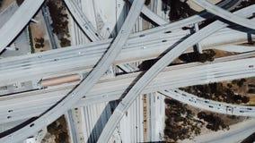 快速地转动在与继续前进多跨线桥、路和桥梁的汽车的大高速公路互换上的顶视图寄生虫 股票录像