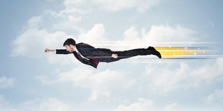 快速地飞行在天空的愉快的商人在云彩之间 图库摄影