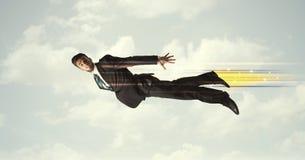 快速地飞行在天空的愉快的商人在云彩之间 免版税库存照片
