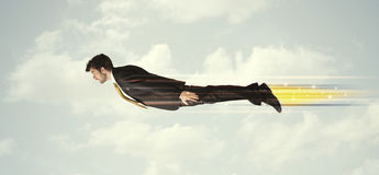 快速地飞行在天空的愉快的商人在云彩之间 免版税库存图片