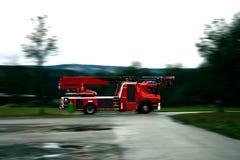 快速地驾驶在一条湿路的消防队员卡车 免版税库存图片