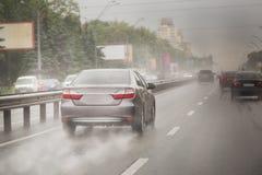 快速地移动在一条高速公路的车在城市在大雨期间 免版税图库摄影
