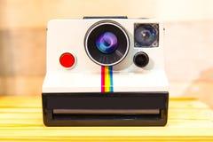 快速照相机或人造偏光板土地照相机在木桌上 免版税库存图片