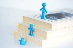 快速的发展概念,在书梯子的孩子演变  免版税图库摄影
