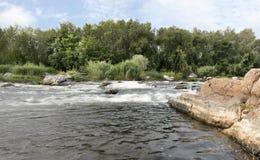 快速的河流程、岩石岸、急流、鲜绿色的植被和多云蓝天在夏天 免版税库存图片