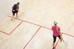 快速的行动的两个女性南瓜球员对壁球球场 免版税库存图片