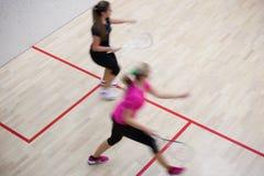 快速的行动的两个女性南瓜球员对壁球球场 免版税库存照片