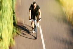 快速的骑自行车者骑马在森林-在看法上的天线里 库存照片