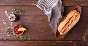 快餐、热狗用黄色芥末和炸薯条 顶视图 免版税图库摄影