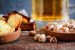 快餐到啤酒、开心果、面包干用莳萝和一个杯子光b 库存图片