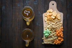 快餐到啤酒和两个杯子低度黄啤酒,在一张木桌上,在酒吧 花生,在壳的花生,鱼,薄脆饼干 顶层 图库摄影