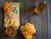 快餐到啤酒和两个杯子低度黄啤酒,在一张木桌上,在酒吧 花生,在壳的花生,鱼,薄脆饼干,池氏 免版税库存图片