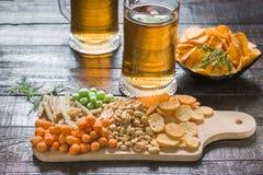 快餐到啤酒和两个杯子低度黄啤酒,在一张木桌上,在酒吧 花生,在壳的花生,鱼,薄脆饼干,池氏 库存图片