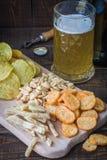 快餐到啤酒和杯子低度黄啤酒,在一张木桌上,在酒吧 花生,鱼,薄脆饼干,芯片 drinki的概念 库存照片