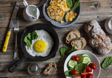 快餐或早餐桌-煎蛋,玉米油炸馅饼,菜,在木背景的家制面包 库存照片