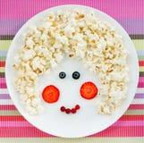 快餐或点心女婴的-甜玉米花用草莓a 库存照片