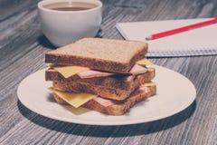 快餐教育快速的速食概念 企业咖啡杯方便问题午餐开张了 与茶的鲜美火腿三明治、笔记本和铅笔 葡萄酒作用, 库存照片